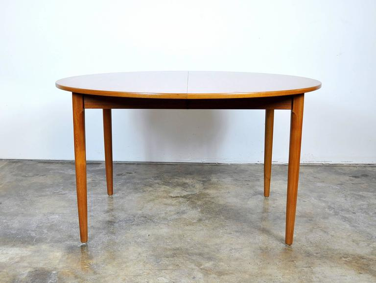 A Mid-Century Danish Modern round dining table manufactured in Denmark by Falster and dating from the 1960s. The table has been professionally refinished and exhibits beautiful grain patterns. It seats four when compact, but can be extended with a