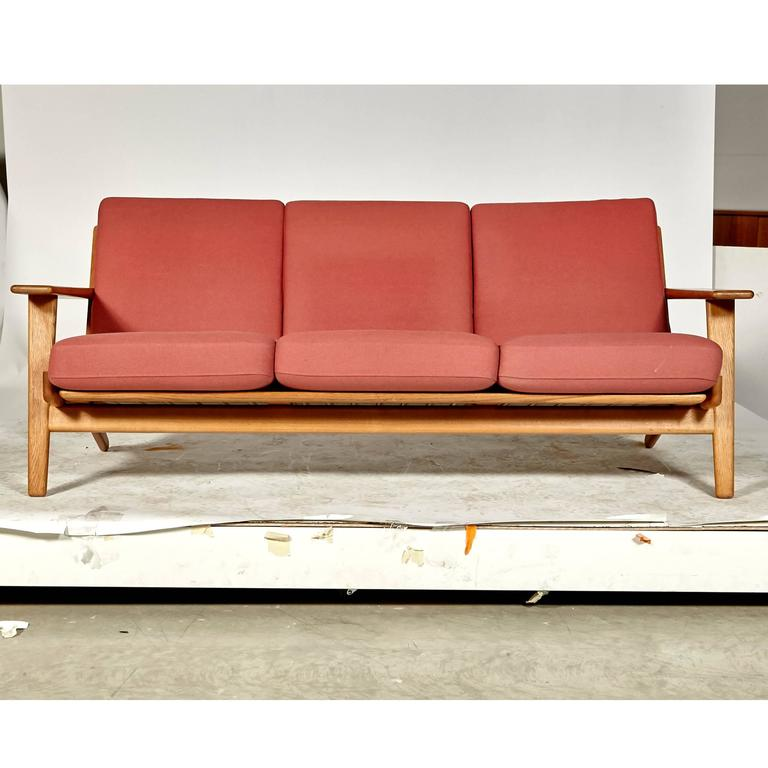 Vintage 1960s Hans J. Wegner three seat sofa designed for GETAMA of Denmark in oak Model GE-290. Sofa has paddle arms and original light red fabric. Arm height: 20.5