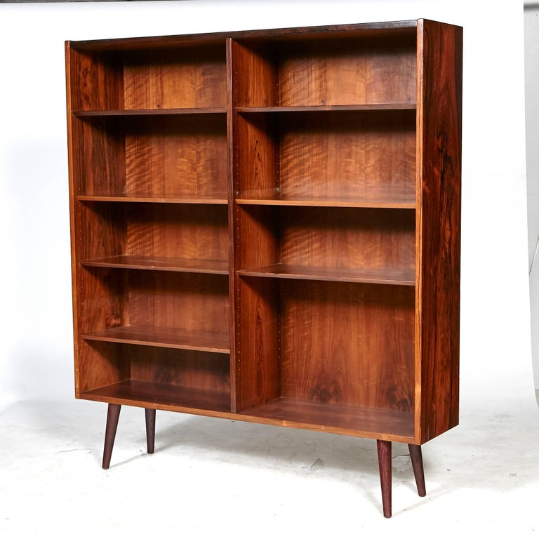 Vintage Scandinavian Modern Danish rosewood bookcase with adjustable shelving and angled round legs. Unmarked.