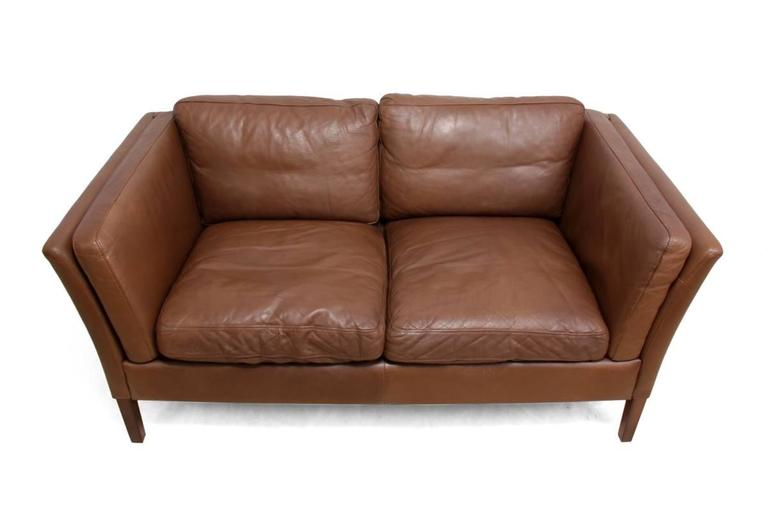 Two-seat leather sofa Danish, circa 1960. This Danish produced leather sofa is in very good condition throughout has some signs of wear Age: 1960 Style: Mid-Century Modern Material: Leather Condition: Very good Dimensions: 74 H x 150 W x 82 D