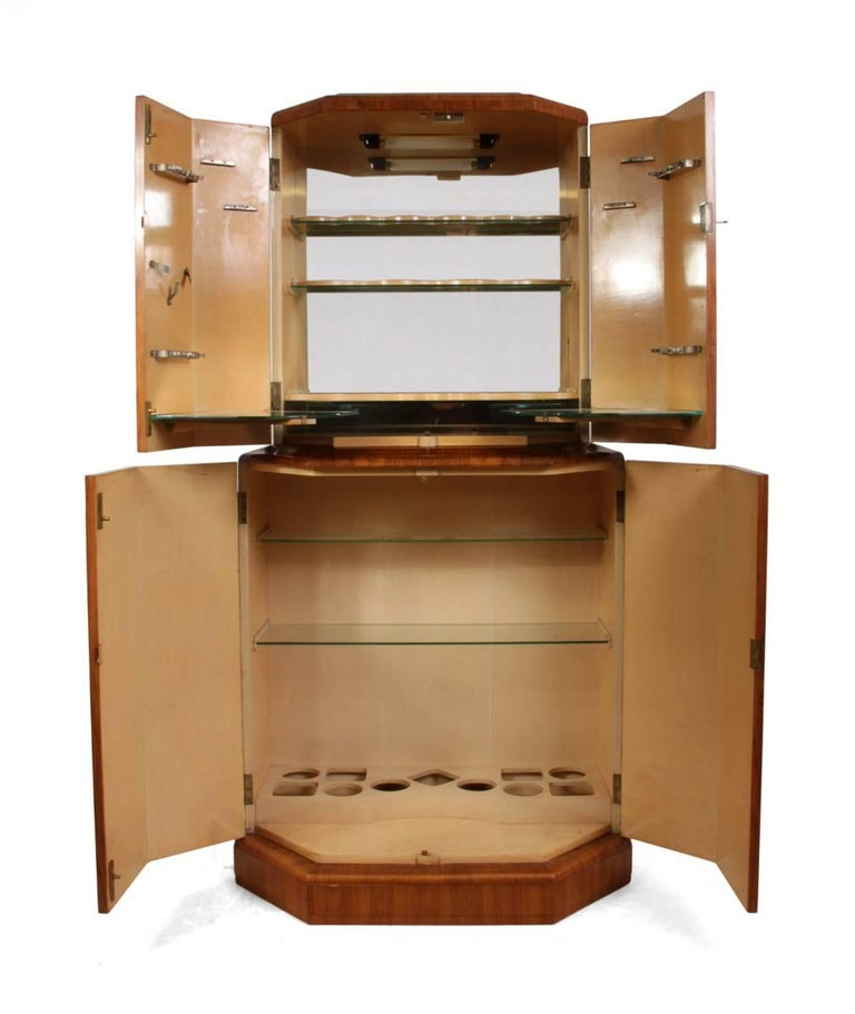 Art Deco cocktail cabinet in walnut, circa 1930 This English cocktail cabinet was produced in the 1930s it is half octagonal shape with lockable doors, the automatic lighting has been re wired, the mirror at the back of the top section has become