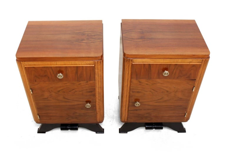 Pair of French Art Deco bedside cabinets A pair of opposite art deco bedside cabinets produced in France in the 1930s. They are single drawer with cupboard below, solid brass hinges and handles. The cabinets have been professionally hand polished