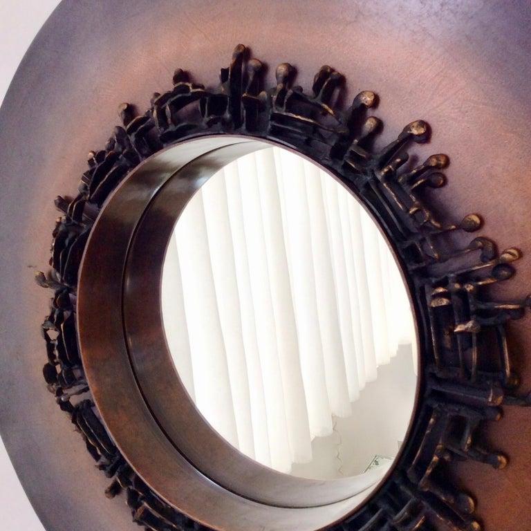 Nice decorative round mirror, circa 1970, France. Bronze patinated metal. Dimensions: Total diameter: 50 cm, diameter of the mirrored glass 23 cm. 7 cm D. Good original condition.                  Burchiellaro style