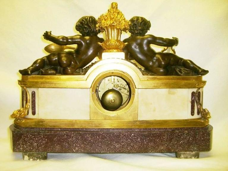 A magnificent 19th century French Louis XVI ormolu and patinated bronze mounted Porphyry clock with two reclining bronze cherubs playing a gilt harp. The movement made by Dargent Medallie Company with silk suspension. Signed by Julien Le
