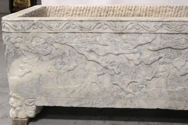 Large impressive 18th century or earlier, continental hand-carved marble planter with carved figural scenes on all four sides resting on four mystical animal feet.