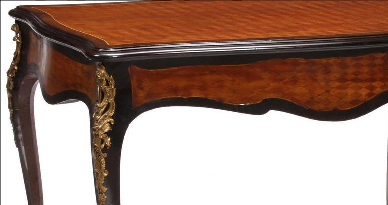 Elegant 19th century French Louis XV style parquetry inlaid kingwood and ebonized bureau plat with fine ormolu mounts. The parquetry top over long hidden drawer all on four cabriole legs mounted with Rocaille gilt bronze mounts and ormolu sabots.