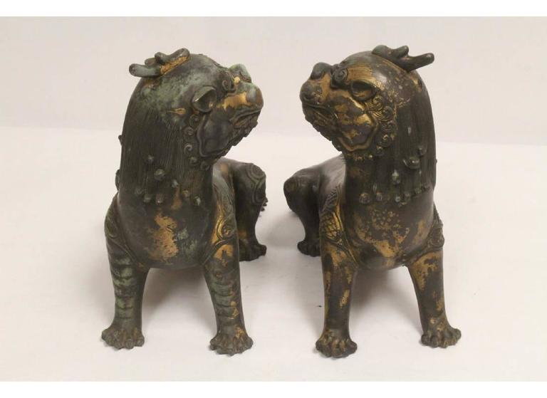 Decorative matching pair of Chinese patinated bronze seated fu lions. Mid-20th century.