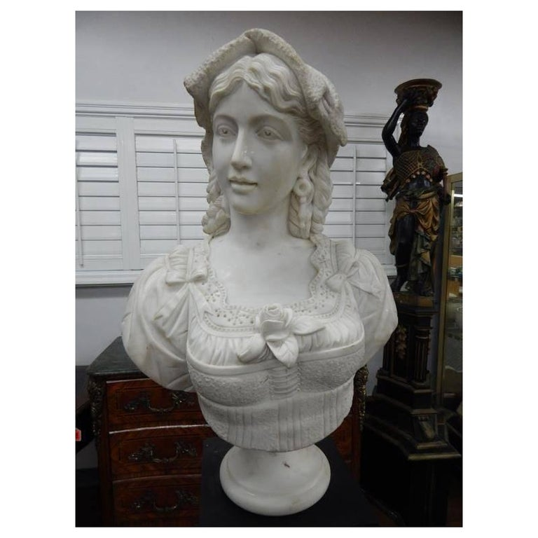 Beautiful Italian carved white marble bust of woman with intricate lace work on her blouse and meticulous attention to detail throughout, rested on black and rouge marble pedestal. Second half of the 20th century. 