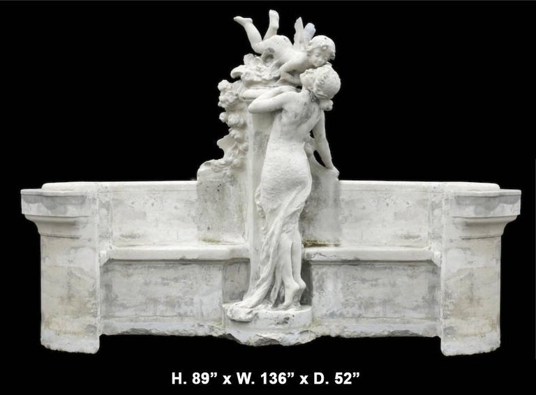 An important and monumental 19th century French figural garden cast stone bench centered by a flying cherub over floral bouquets and kissing a young maiden in a long beautiful dress. The bench also features concave sides on the outer rim of the