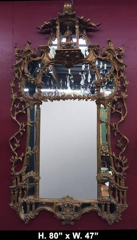 Exceptional 19th century George III style Chippendale style carved giltwood mirror. The work is surmounted by an intricately carved balcony encasing a small gilt musician with musical instrument over mirror surrounded by carved laurel leaves with