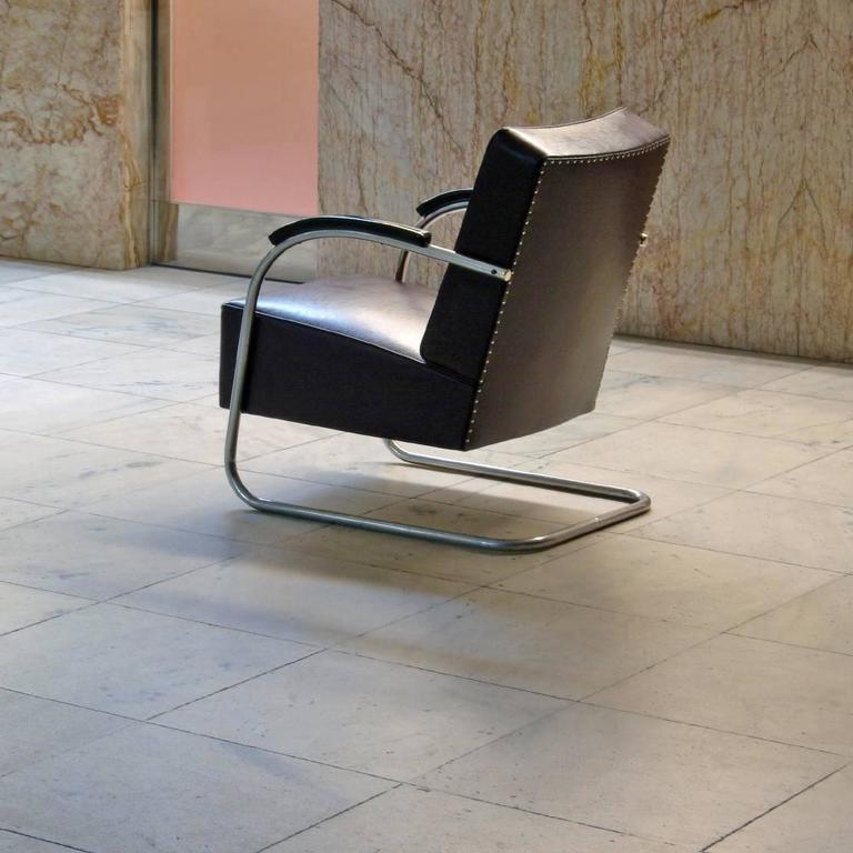 """A low tubular steel cantilever armchair made of chrome-plated tubular steel in a single open continuous line. This elegant original """"Freischwinger"""" easy chair with armrests is restored on request and available in different amounts."""