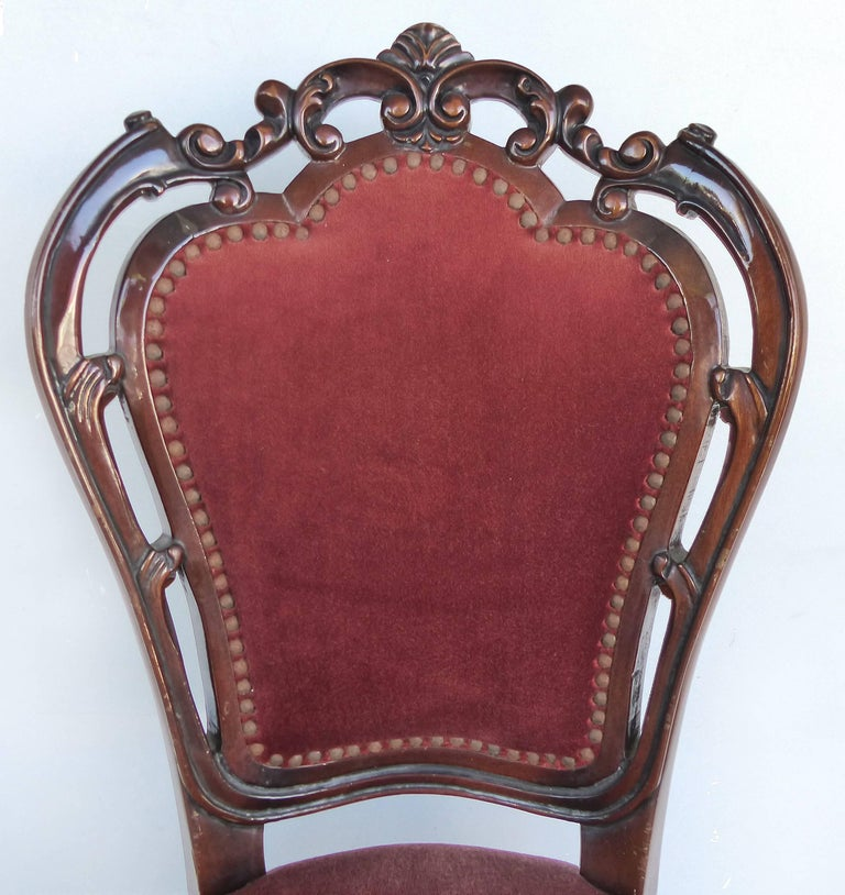 Offered for sale is a set of ten Louis XV style mahogany dining side chairs with pierced open carved backs, velvet mohair upholstery and brass nailheads. The chairs are in good condition with one having a hole to the seat fabric as shown. Measures: