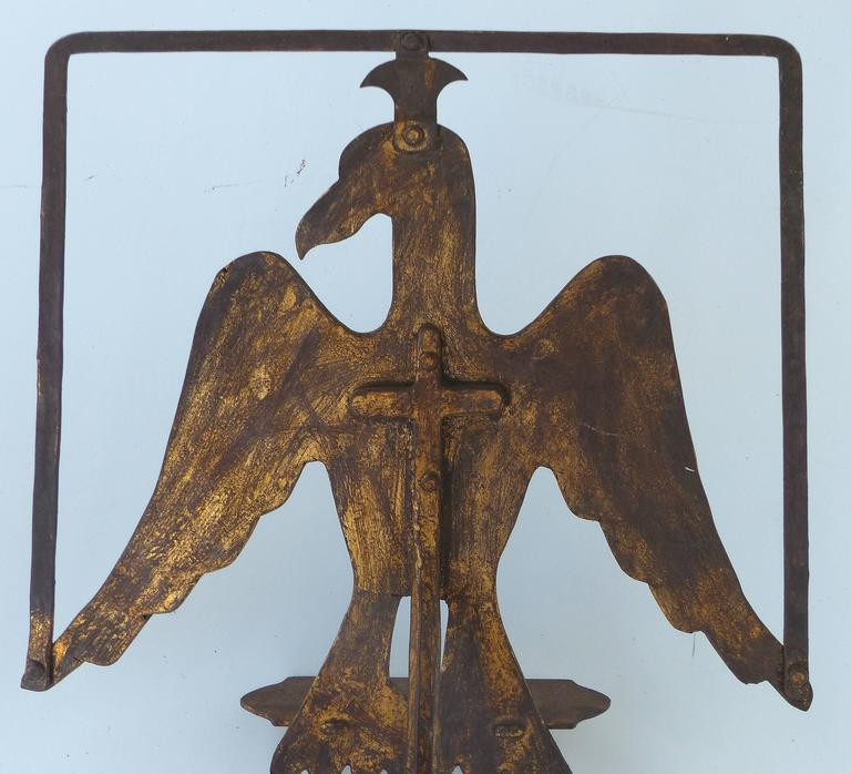 An early 20th century gilt-iron book stand with an eagle motif. Supported by a three-leg pedestal form, the iron has achieved an aged patina with remnants of the original gilt finish remaining.