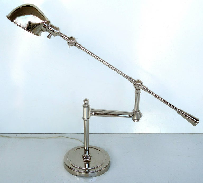 Fine Quality Adjustable Chrome Task Lamp with Pivoting Arm  Offered for sale is an adjustable chrome desk lamp with a pivoting arm and adjustable shade. This is a substantial, heavy and fine quality lamp. Wired and in working condition and uses a