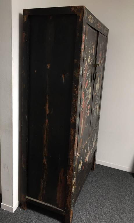 A decorated early 20th century wedding cabinet. Two center doors open outward revealing two shelves. All original material. Exterior decorated with drawings depicting birds, branches and flower motifs. 74