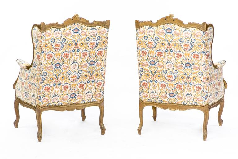 A stunning pair of 19th century Louis XV style French wingback armchairs upholstered in luxurious floral pattern, circa 1870. This piece is made of heavily carved walnut with a gold finish. Both of the items are in excellent condition.