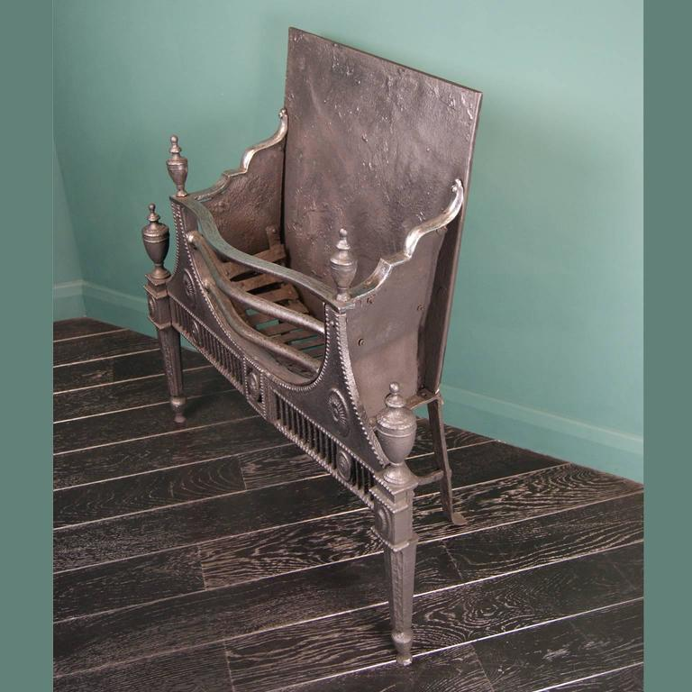 An 18th century cast and wrought iron neoclassical period fire grate. This grate has a decorative cast-iron front with bead, oval and flute detailing holding a semi-circular polished wrought iron basket. Tapered legs with urn finials uppermost and
