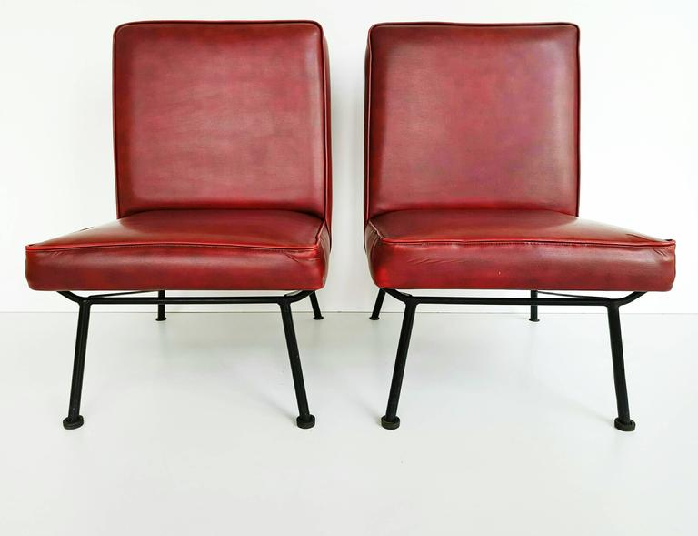 Beautiful pair of French lounge chairs manufactured in 1950s, with is original burgundy leatherette, in very good vintage condition. Very nice iron base.
