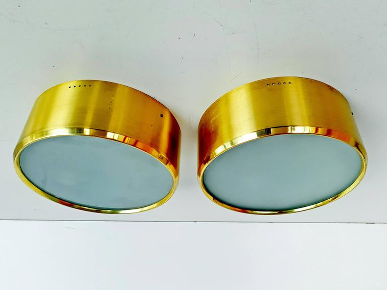 Rare pair of ceiling/wall lights manufactured by Stilnovo in Italy, circa 1960s. Brass, painted aluminum and textured glass. Two bulbs per sconce.