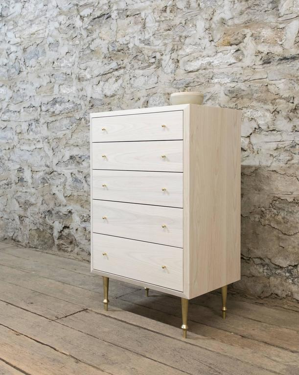 Solid bleached ash with turned brass legs and drawer pulls.