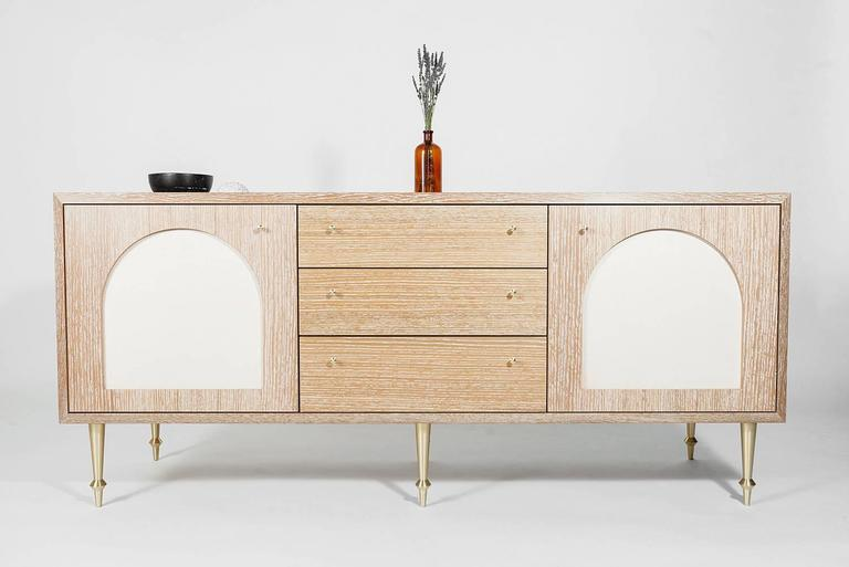 As shown: Solid white oak with white oak veneer and cerused finish. Turned brass legs and drawer pulls Swing doors and inset leather panels Oil and wax cerused finish  Dimensions: 28 1/4