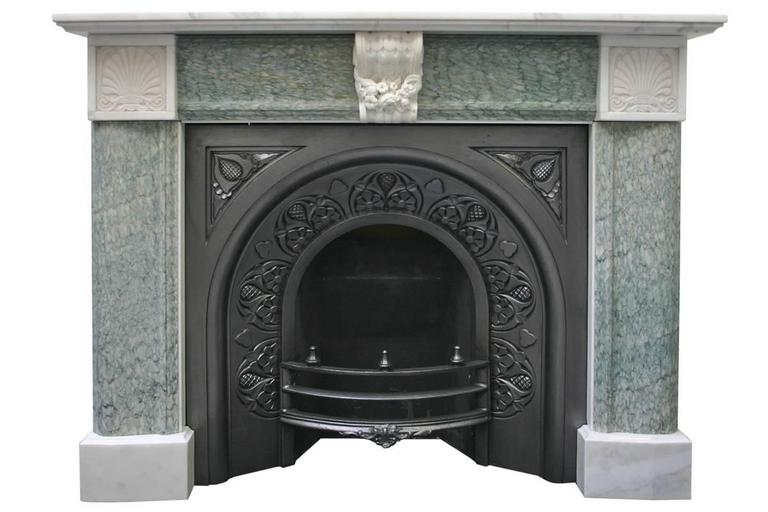 Antique 19th Century Regency marble fire surround. Plain statuary marble plinths support green Campan marble bolection jambs terminating in statuary marble end blocks carved with an anthemion design. The frieze is green Campan marble bolection