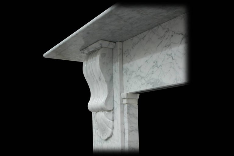 Antique 19th century Victorian marble fire surround of good figured Carrara marble with carved corbels supporting the shelf and a break front frieze.  circa 1870.  For sizes please see final image