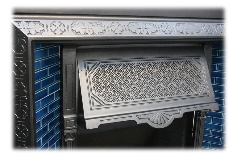 Reclaimed late Victorian cast iron fireplace grate. Circa 1895. Complete with a set of original fireplace tiles.  This grate has been finished the traditional black grate polish, leaving a gun metal / pewter shine. Alternative finishes are
