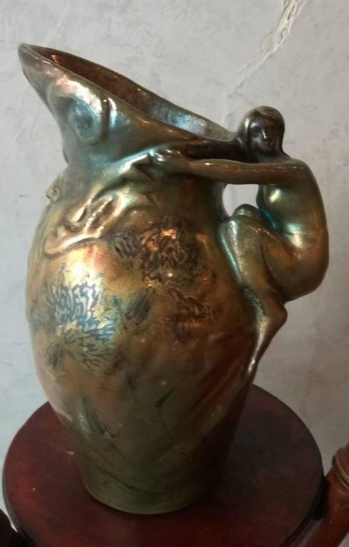 This beautiful Art Nouveau ewer in stoneware is signed by Delphin Massier. It is distinguished by an original, anthropomorphic form the ewer represents a man head and the handle is materialized by a woman dressed in a drape. A decor of flowers is