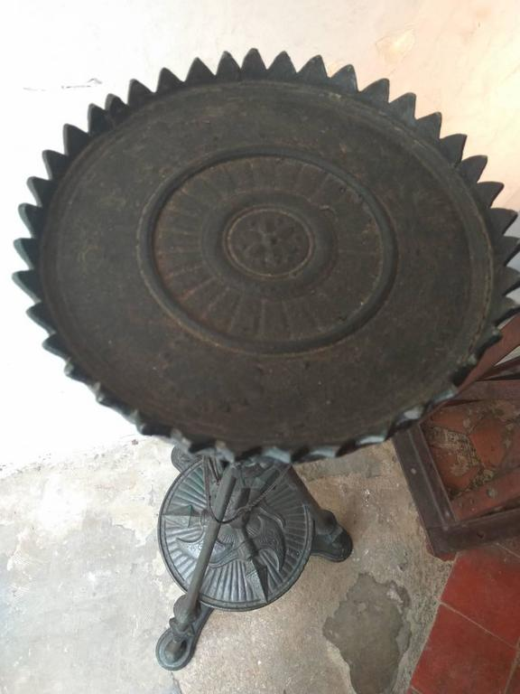 This tripod pedestal is based on halberd feet which crisscross to support the upper tray with saw tooth edge. In the pedestal's lower part, a cast iron disc, which evokes a shield, gets into the weapon guards. This tray is ardoned with rays