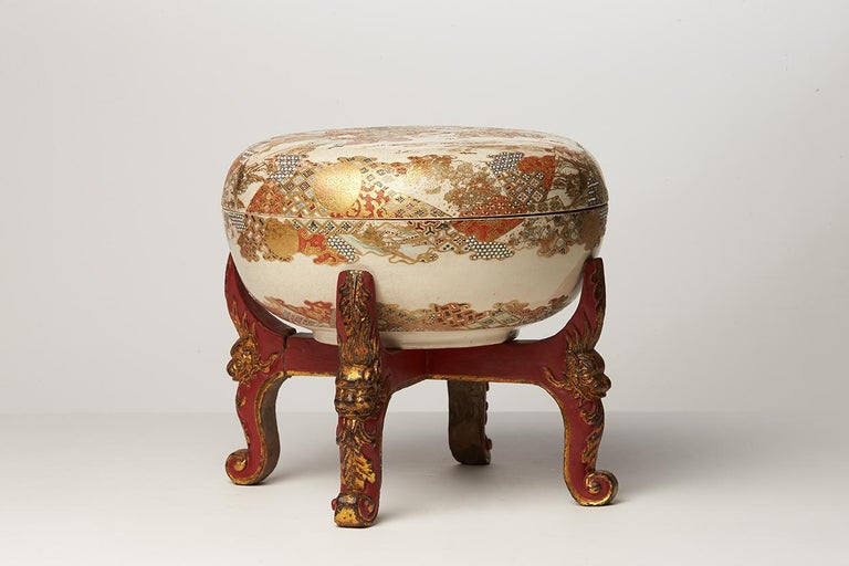 Round Satsuma ware box painted in polychrome enamels and gold. The top of the lid is decorated with Japanese characters in a landscape. The interior of the lid is decorated with another landscapes, birds and trees, in Japanese prints style. The
