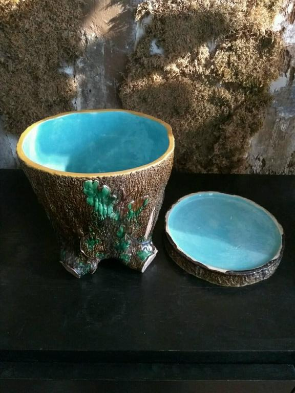 This planter imitates a tree stump. Its centre is enameled with a luminous blue which is a characteristic of the English manufacture. This color serves as a signature and brings a very decorative touch to the piece The subject of the tree stump was
