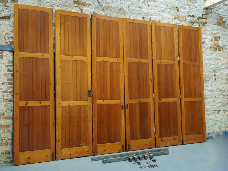 An amazing set of six rare 1960s reclaimed / salvaged solid oregon pine room dividers / hinged bi-folding doors.  These used to partition off a large hall space when needed with the option of using a fixed single door as access when closed.