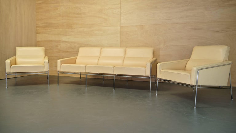 Pair of Arne Jacobsen series 3300 lounge chairs and 3303 sofa in cream premium leather.  Design: Arne Jacobsen. Manufactured in Denmark by Fritz Hansen.  Chair dimensions: Height 72 cm, depth 79 cm, width 73 cm.  Sofa dimensions: Height 72