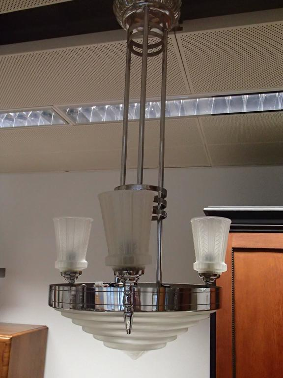 Chandelier by G. Leleu signed with a beautiful center bowl in clear frosted molded glass with ribbed and geometric motif. Polished details on a nickel bronze frame. Re-plating upon request.