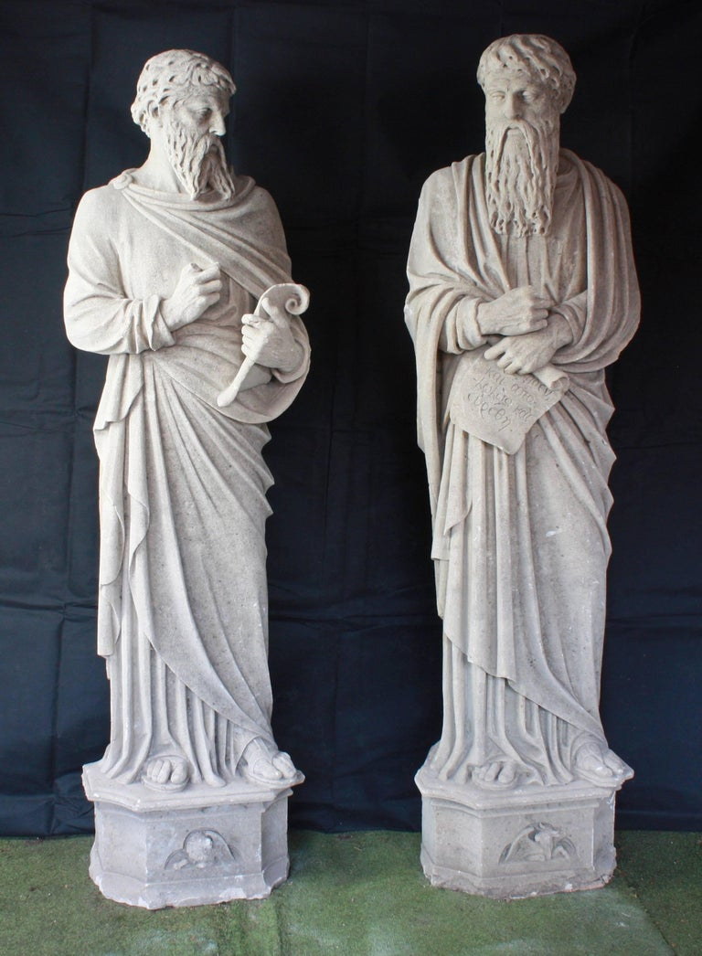 A stunning and monumental pair of carved stone statues, depicting Saint Peter and Saint Paul.