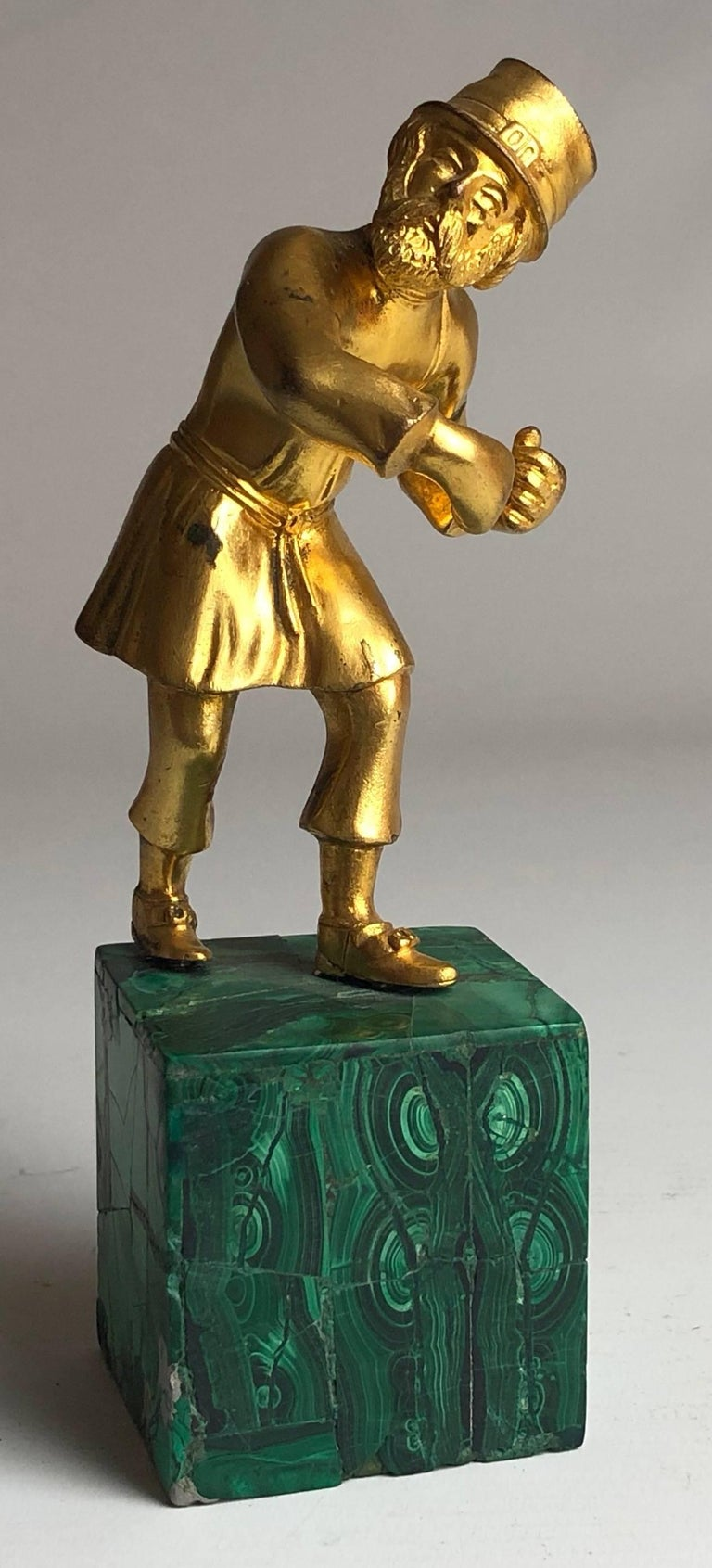 An early 20th century Russian gilded bronze, finely modelled as a traditional Cossack, on a Malachite base,  Russian, circa 1900.  Measure: He stands 6