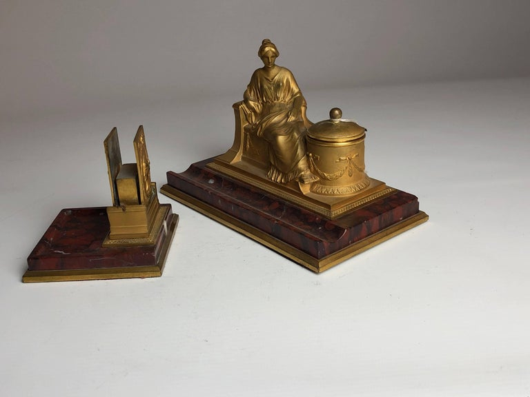 A lovely matching desk set comprising of a figural bronze inkwell with a matching match case and striker, both sat on reuge marble bases.