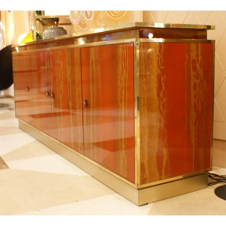 Fine sideboard by Maison Jansen, France, 1970. This four doors sideboard is red lacquered with etched effect that goes to the gold. The sideboard has the details in brass.