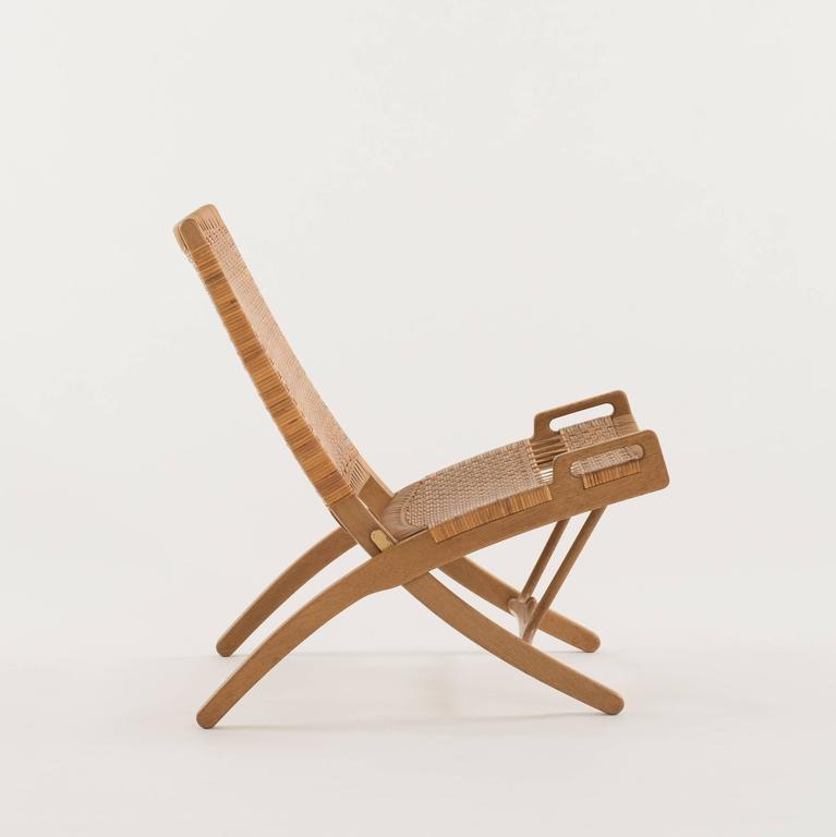 Hans J. Wegner folding chair of oak model JH-512, 1949. Executed by Johannes Hansen, Copenhagen, Denmark.   Pair of folding chairs with hanging bracket available.