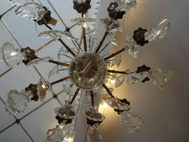 Antique French prism filled chandelier with a dark bronze patina. Wonderfully ornamental flat leaf glass prisms, in different sizes. Holds ten candle shaped light bulbs.