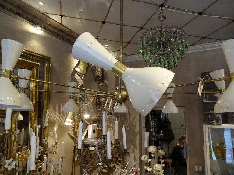 Gigantic and fabulously classic ceiling light, in 1950s Italian novo style. Stunning brass frame and white metal shades, with eight movable lampshades and light sources at both ends. Wonderful iconic and eye catching piece.  Measures: height 120 x