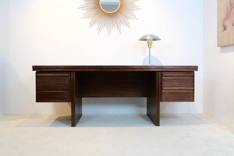 Beautiful Dutch teak executive desk coming from the executive room belonging to the old Philips Electronics Company in the Netherlands. This desk is really heavy duty and in a very good condition. It comes with four drawers and the finishing is