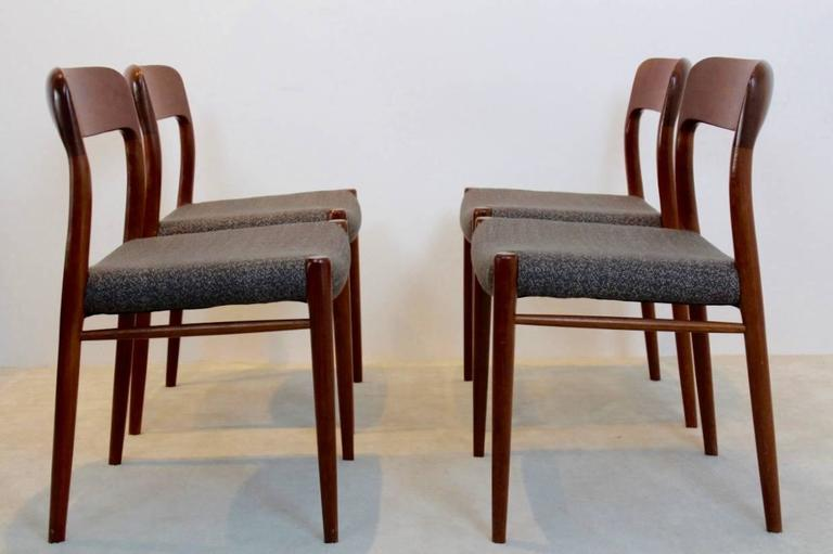 Set of four dining chairs designed by Niels Otto Møller and manufactured in Denmark by J.L. Møllers Møbelfabrik A/S during the 1950s. Each chair features sculpted teak backrests and has been recently reupholstered with high quality 'Ploeg fabric'.