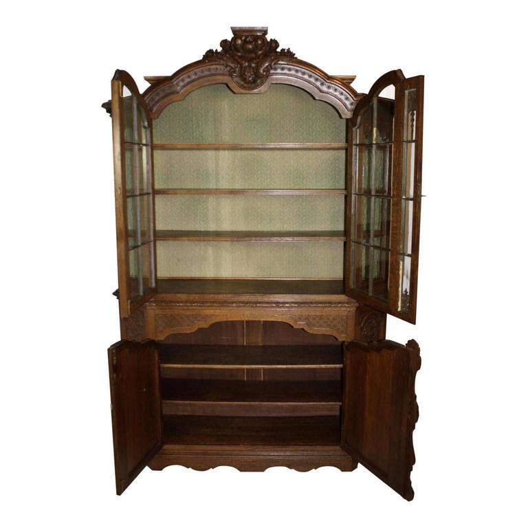 This substantial, quarter sawn oak, hutch has seven shelves with upper glass display comprised of windowed glass panels, floral, leaves and shell carvings in the reliefs with simple skirt detailing. The fabric covering in the upper display case can