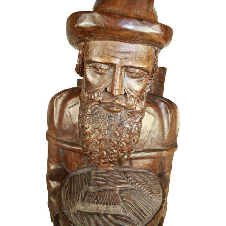An elderly, bearded, Asian man carries a bowl of food, possibly noodles, with two mats tied to his back. Carved from a substantial piece of teak, this somber carving stands at almost 3 and a half feet tall.