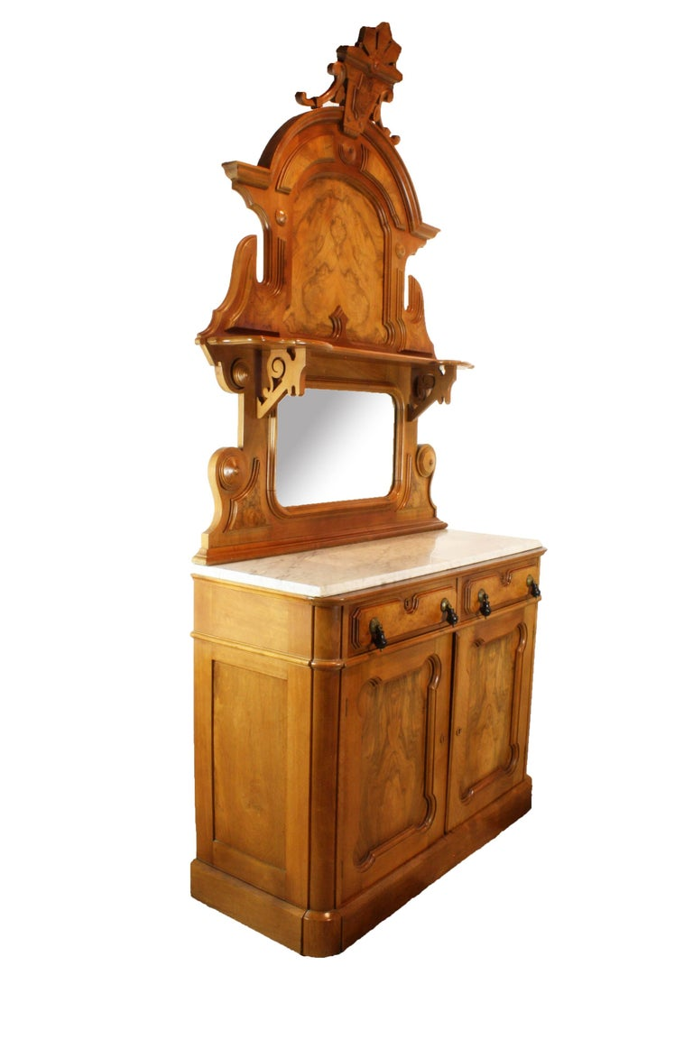 Mirrored burled walnut panels adorn this handsome American buffet in the Eastlake Victorian style.  Two drawers, one compartmentalized, and a lower cabinet with one shelf, offer storage.  The counter top is white marble. The eye is drawn up the