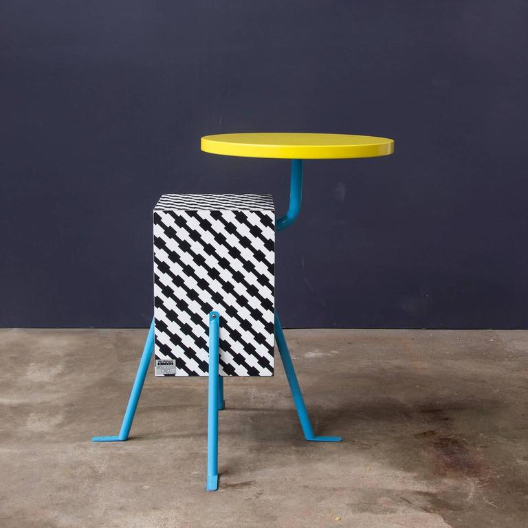"""From the inaugural 1981 Memphis collection, this very popular design by Michele de Lucchi (one of the founding members of the design collective) implements a de Lucchi laminate design named """"Terrific"""". Beneath its bright yellow lacquered"""
