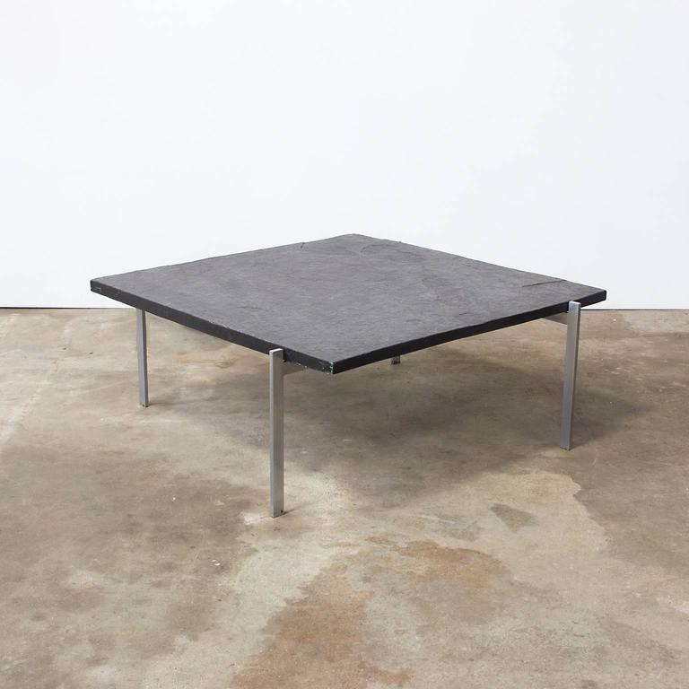 Coffee table designed by Poul Kjærholm in 1956. Matte chrome-plated steel frame, slate top.  Measures: Slate tabeltop is 80 cm x 80 cm x 3cm  Weight: Ca 35 kg.  Free shipping for Amsterdam, Haarlem and IJmuiden for lamps, chairs, small items as