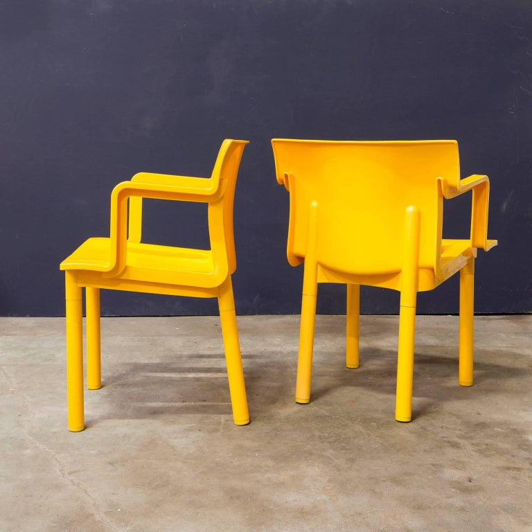 """Set of seven rare yellow Kartell stackable plastic chairs. Castelli Ferrieri's Chair 4870 was awarded the Compasso d'Oro in 1986 for harmoniously balancing """"purpose, economy and technology."""". The chairs show traces of usage like some scratches at"""